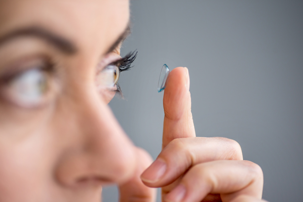woman putting her scleral contact into her eye