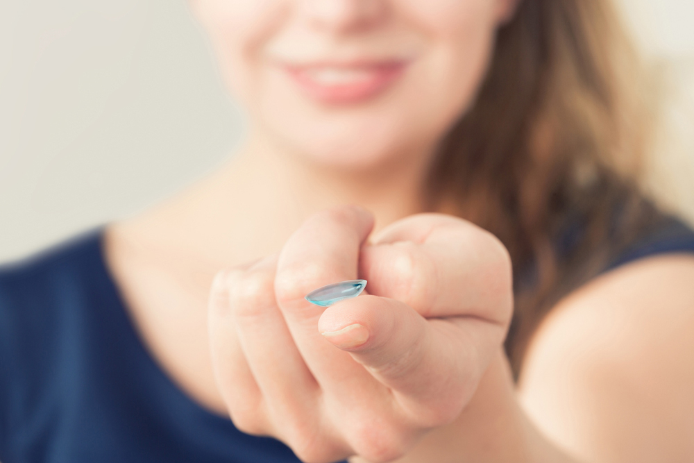woman holding a contact lens for dry eyes